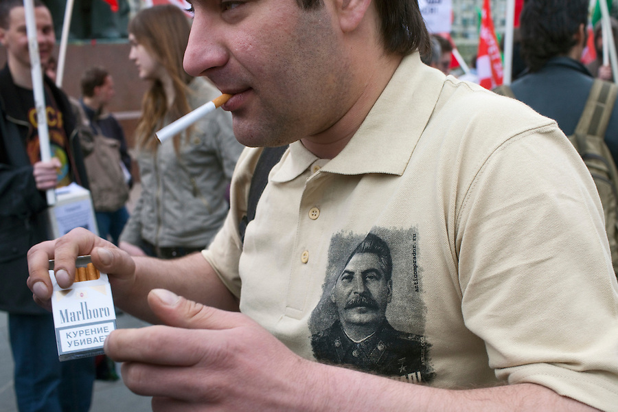 Moscow, Russia, 01/05/2011..A demonstrator wearing a shirt with Stalin's picture lights a Marlboro cigarette as a mixture of Communist and anarchist anti-government groups demonstrate in central Moscow. A variety of political groups took to the streets on the traditional Russian Mayday holiday.