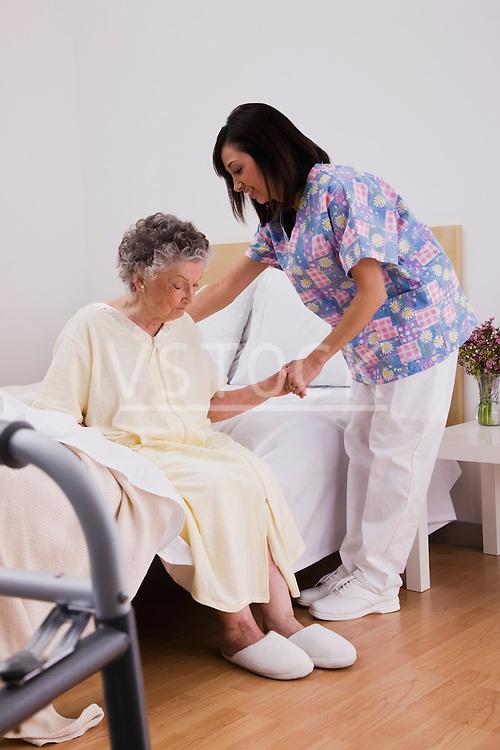 Female nurse assisting senior woman on bed