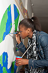 high school teenager at work painting poster on world peace and racial harmony in corridor