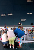 Photo by Rick WIlson--2/1/03--Three women place flowers in front of the Astronauts Memorial to honor the memory of the Space Shuttle Columbia crew who perished Saturday morning above Texas while enroute to landing at Kennedy Space Center at Cape Canaveral. The names of astronauts killed before them are displayed on the black granite panels of the monument above the women..