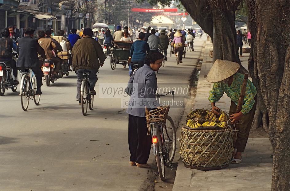Asie/Vietnam/Hanoi: Cyclistes dans la rue prés du temple de la Littérature - femme achetant des bananes