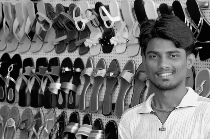 A happy shopkeeper in central Mumbai, selling women shoes, Mumbai, India