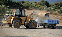 Pictured: A digger loads a tipper lorry with soil from the second site to be transported to the farmhouse so that specialist officers search through it in Kos, Greece. Monday 10 October 2016<br />Re: Police teams led by South Yorkshire Police are searching for missing toddler Ben Needham on the Greek island of Kos.<br />Ben, from Sheffield, was 21 months old when he disappeared on 24 July 1991 during a family holiday.<br />Digging has begun at a new site after a fresh line of inquiry suggested he could have been crushed by a digger.