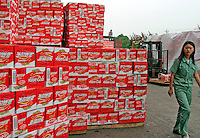 A worker walks past a mountain of Future Cola cases at the Wahaha Beverage Manufacturing Base in Hangzhou, China. The privately owned Wahaha group is the largest beverage manufacturer in China with a total production of 3.75 million tons in assorted beverages last year. The group has recently decided to ship nearly 15 thousand cases of its Future Cola to the U.S..07-JUN-04