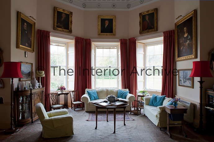 A spacious living room lit with three Georgian sash windows