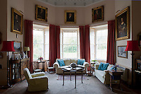 A spacious living room lit with three Georgian sash windows