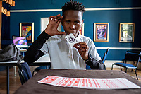 Duma Mgqoki, a student at the Cape Town College of Magic, practices a card trick in an empty classroom.