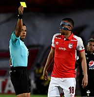 BOGOTÁ-COLOMBIA, 09-11-2019: Bismarks Santiago, árbitro muestra tarjeta amarilla a Daniel Giraldo de Independiente Santa Fe, durante partido de la fecha 1 de los cuadrangulares semifinales entre Independiente Santa Fe y América de Cali, por la Liga Águila II 2019, jugado en el estadio Nemesio Camacho El Campín de la ciudad de Bogotá. / Bismarks Santiago, referee shows yellow card to Daniel Giraldo of Independiente Santa Fe, during a match of the 1 date of the semifinals quarter finals between Independiente Santa Fe and America de Cali, for the Aguila Leguaje II 2019 played at the Nemesio Camacho El Campin Stadium in Bogota city. / Photo: VizzorImage / Luis Ramírez / Staff.