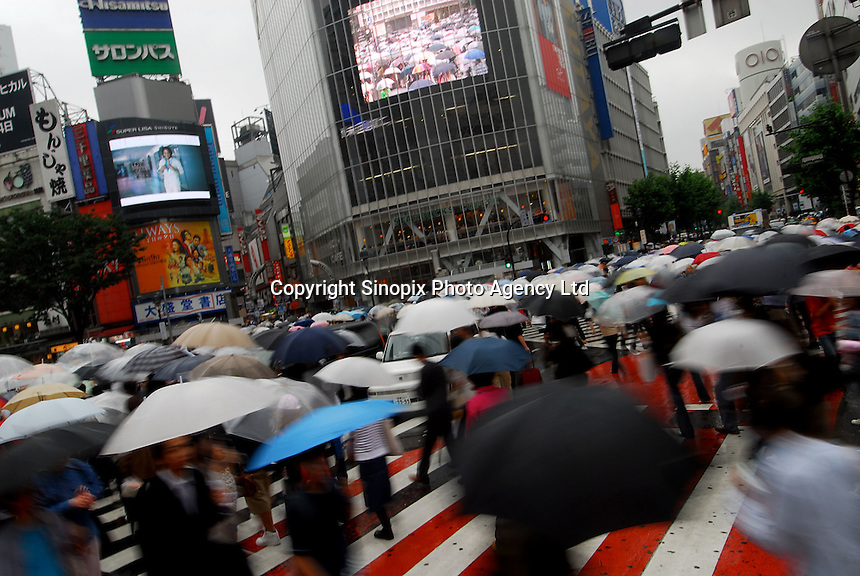 People cross the the busy shibuya road junction in the rain in Tokyo, Japan..10 Jun 2006