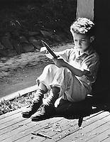 Boy whilttling a stick.