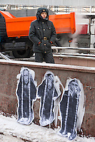 """Moscow, Russia, 04/02/2012..A Russian policeman standing behind graffiti depicting Prime Minister Vladimir Putin as the three monkeys """"Hear no evil, see no evil, speak no evil"""" watches as tens of thousands of demonstrators march in central Moscow and protest against election fraud and Prime Minister Vladimir Putin in temperatures of -20 centigrade. Organisers claimed an attendance of 130,000 despite the bitter cold."""