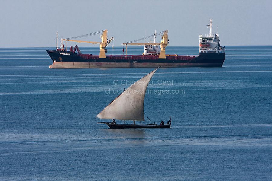 Zanzibar, Tanzania.  Cargo Freighter and Traditional Dhow Share the Harbor in Zanzibar.
