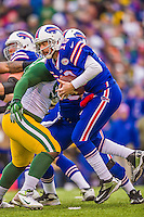 14 December 2014: Buffalo Bills quarterback Kyle Orton is hit for an 8-yard loss in the first quarter against the Green Bay Packers at Ralph Wilson Stadium in Orchard Park, NY. The Bills defeated the Packers 21-13, snapping the Packers' 5-game winning streak and keeping the Bills' 2014 playoff hopes alive. Mandatory Credit: Ed Wolfstein Photo *** RAW (NEF) Image File Available ***
