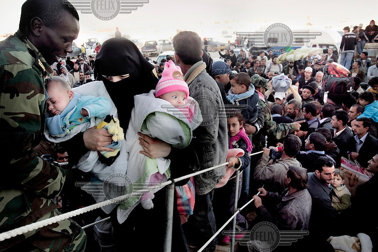 A Libyan soldier helps a woman carry her children as he helps to process thousands of Syrian refugees as they try to escape Libya at the port in Benghazi. Syria has sent ships to pick up their citizens, but there's only room for 1000 in each. Today they sent three ships and tomorrow there will be more. The Syrian government promises that all Syrians will be evacuated. On 17 February 2011 Libya saw the beginnings of a revolution against the 41 year regime of Col Muammar Gaddafi.