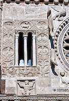13th century reilief sculpture depicting the Kingdom of Good and salvation with Atlas at the bottom symbolically holding up the church which is represented at the top by the Lamb of God with 2 angels on either side and the four Fathers of the church in round panels running down either side of the central window, of the 8th century Romanesque Basilica church of St Peters, Tuscania, Lazio, Italy