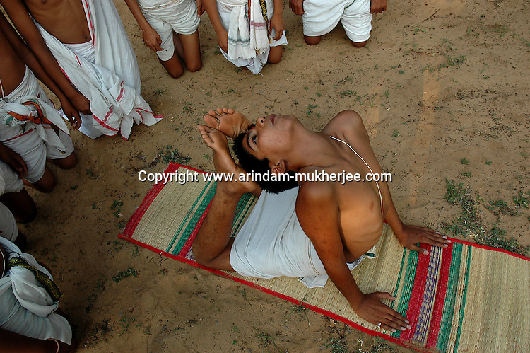 """Students of Om Shantidhama practicing """"yoga"""". Om Shantidhama is a residential vedic school for boys. Nestled among the confluence of hills, forest and rivers - Om Shanti Dhama is a world removed from the maddeningly fast and often chaotic urban India. Students from allover the country are selected to take part in its Vedic and free education system. What is unique about this institute is that they have blended the traditional and modern education system. Here computer and science is taught with the same passion as the Vedas and Shastras, helping the students to grow spiritually as well as earn a living. Bonding with the nature and animal world is a mandatory part of the institute's curriculum. Karnataka, India. Arindam Mukherjee"""