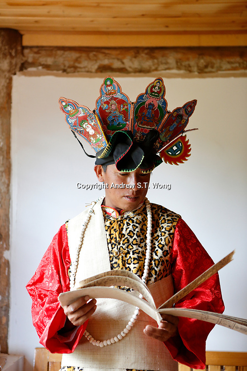 Wumu Village, Yulong County, Yunnan Province, China - Dongba priest He Jixian of the Naxi ethnic group wearing his traditional priest costumes reads scripture, June 2019.