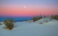 The full moon rises during sunset at White Sands National Monument, New Mexico