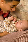3 month old baby boy inteaction with 15 year old teenage half brother vertical  Hispanic Puerto Rican