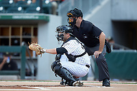 Charlotte Knights catcher Brett Austin (22) sets a target as home plate umpire Brian Peterson looks on during the game against the Indianapolis Indians at BB&T BallPark on May 26, 2018 in Charlotte, North Carolina. The Indians defeated the Knights 6-2.  (Brian Westerholt/Four Seam Images)