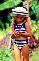 Young girl, age 5, walking outdoors in swim suit and sailor hat