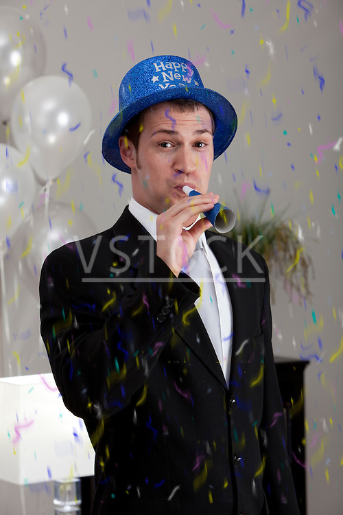 Young man celebrating birthday, blowing