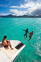 Young women jumping off stern of catamaran into crystal clear lagoon