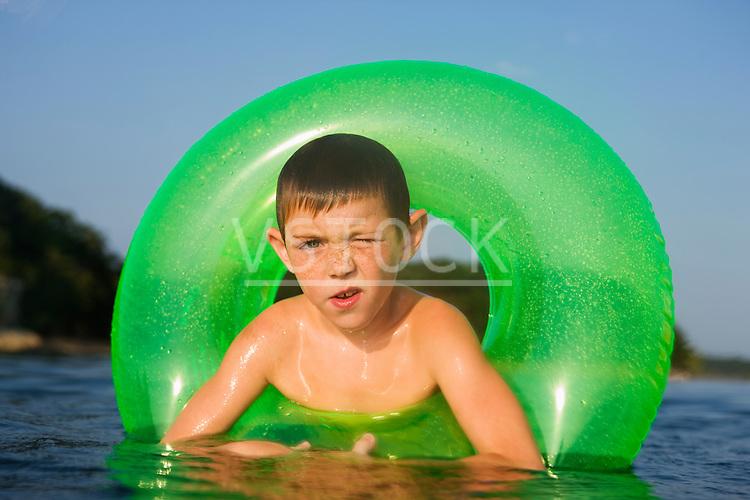USA, Missouri, Stockton, Stockton Lake, boy (6-7) swimming in inflatable ring