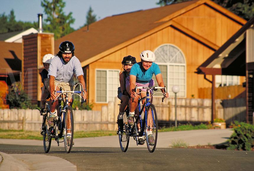 family of four riding tandem bicycles through a suburban neighborhood. family. California USA.