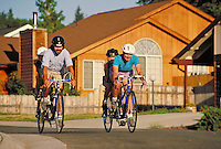 family of four riding tandem bicycles through a suburban neighborhood. family. California USA.