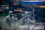 A pedestrian wearing a face mast is reflected in a  window of the Nasdaq MarketSite as monitors display stock market information in New York, U.S., on Thursday, March 19, 2020. New York state Governor Andrew Cuomo on Thursday ordered businesses to keep 75% of their workforce home as the number of coronavirus cases rises rapidly. Photograph by Michael Nagle/Redux