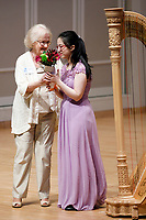 USA International Harp Competition Vice President Linda Wood Rollo, left, gives flowers to performer Hanjiao Zou during the Stars of Tomorrow Concert at the 11th USA International Harp Competition at Indiana University in Bloomington, Indiana on Thursday, July 11, 2019. (Photo by James Brosher)