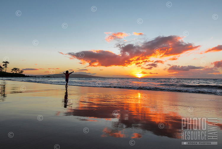 A young girl opens her arms to the setting sun, Wailea Beach, Maui.