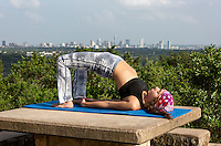 Young woman performing yoga bridge pose on top of Mount Bonnell overlooking the Austin skyline.