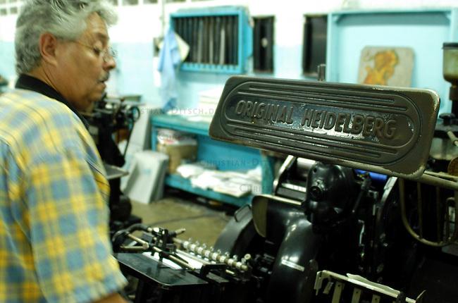"""Duckereikollektiv in Caracas<br /> Das Druckereikollektiv """"Instituto Municipal de Publicaciones"""" wurde 2003 von linken Arbeiterinnen und Arbeitern gegruendet. Schon drei Jahre zuvor, 2000, war die Druckerei von einigen sozialen Aktivisten uebernommen worden. Damals hatte die Druckerei absolut unwirtschaftlich und zu schlechten Bedingungen fuer die Arbeiterinnen und Arbeiter mit 160 Beschaeftigten produziert. Heute arbeiten hier ca. 250 Frauen und Maenner, die gute Auftragslage erfordert inzwischen ein Dreischichtsystem mit je 7 Stunden inclusive Pausen. Die Werksleitung muss genauso wie die Arbeiter an bei jeder Schicht anwesend sein.<br /> Die Druckerei stellt Publiaktionen fuer linke Gruppen, Stadtteilgruppen im ganzen Land und die Stadtverwaltung von Caracas her.<br /> Auf dem Firmengelaede wurde zur medizinischen Versorgung des Stadtteils eine Station des Gesundheitsprogrammes """"Barrio Adentro"""" eingerichtet. Hier gibt es kostenlos u.a. zahnaerztliche und gynokologische Versorgung.<br /> Hier: Ein Drucker arbeitet an einer Tiegeldruckmaschine der Marke Heidelberger die vom Anfang des 20. Jahrhunderts stammt.<br /> 8.11.2004, Caracas / Venezuela<br /> Copyright: Christian-Ditsch.de<br /> [Inhaltsveraendernde Manipulation des Fotos nur nach ausdruecklicher Genehmigung des Fotografen. Vereinbarungen ueber Abtretung von Persoenlichkeitsrechten/Model Release der abgebildeten Person/Personen liegen nicht vor. NO MODEL RELEASE! Nur fuer Redaktionelle Zwecke. Don't publish without copyright Christian-Ditsch.de, Veroeffentlichung nur mit Fotografennennung, sowie gegen Honorar, MwSt. und Beleg. Konto: I N G - D i B a, IBAN DE58500105175400192269, BIC INGDDEFFXXX, Kontakt: post@christian-ditsch.de<br /> Bei der Bearbeitung der Dateiinformationen darf die Urheberkennzeichnung in den EXIF- und  IPTC-Daten nicht entfernt werden, diese sind in digitalen Medien nach §95c UrhG rechtlich geschuetzt. Der Urhebervermerk wird gemaess §13 UrhG verlangt.]"""