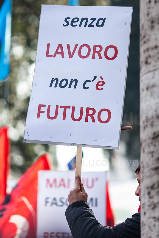 """Unknown, Protester, """"Without Work There Is No Future"""".<br /> <br /> Rome, 01/05/2019. This year I will not go to a MayDay Parade, I will not photograph Red flags, trade unionists, activists, thousands of members of the public marching, celebrating, chanting, fighting, marking the International Worker's Day. This year, I decided to show some of the Workers I had the chance to meet and document while at Work. This Story is dedicated to all the people who work, to all the People who are struggling to find a job, to the underpaid, to the exploited, and to the people who work in slave conditions, another way is really possible, and it is not the usual meaningless slogan: MAKE MAYDAY EVERYDAY!<br /> <br /> Happy International Workers Day, long live MayDay!"""