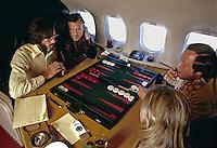 Hugh Hefner plays backgammon aboard his lear jet. 1973. Photo by John G. Zimmerman.