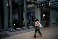 NEW YORK, NY - AUGUST 31: A woman passes by the TESLA store on August 31, 2020 in New York City. Tesla shares are more affordable today after their split, which does not make the stock a more attractive investment than it was pre-split price. (Photo by Eduardo MunozAlvarez/VIEWpress)