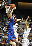 Bishop Gorman's Gio Guzman shoots past Hug defenders Samuel Williams, center, and Robin Dhatt during the NIAA 4A State Basketball Championship game between Bishop Gorman and Hug high schools at Lawlor Events Center, in Reno, Nev, on Friday, Feb. 24, 2012. Bishop Gorman won 96-51..Photo by Cathleen Allison