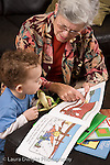 2 year old toddler boy at home with grandmother interaction read to from picture book language development grandmother pointing at illustration vertical she takes care of him when parents work