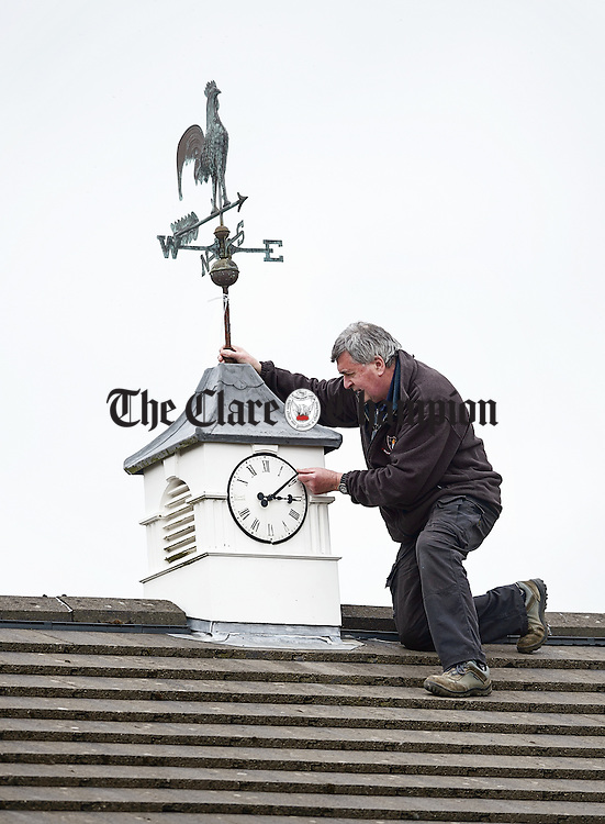 David O Connell, maintenance man at Ennis Community College sets the clock on the roof to new time while accessing the roof is still safe ahead of a break in the weather. It's the Kilmihil native's final time doing this job as he will be retiring in June after 37 years service. Photograph by John Kelly.
