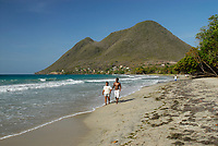 Two people walking on the sandy beach in a cove named Anse d'Arlet in Martinique island which is an overseas region of France, French Island, Caribbean Sea