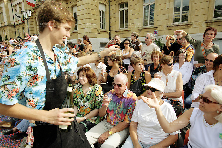 Switzerland. Canton of Neuchâtel. Neuchâtel. Grape Harvest Festival. A young man offers free glasses of local wine to the Public. © 2006 Didier Ruef