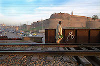 A man walks on a train line next to the Grand Trunk Road as it passes the Bala Hisar Fort in Peshawar, North-West Frontier Province built by the Sikhs in 1834 during their rule.