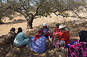 "Morocco - Tidzi - Members of the Ajddigue cooperative sit under the shade of the Argan tree for a lunch break. The cooperative produces around 20 tons of argan oil per year, with a turnover of around 100,000 euros. Despite having contributed to the empowerment of thousands of rural women, the argan oil cooperatives are now threatened by the industrial plants set up in Casablanca and Agadir, which are able to extract much more oil in less time. ""Our cooperatives might disappear in 5 or 10 years"" confesses Zahra Knabo, the director at Ajddigue."