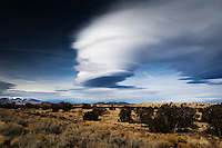 Spinning out cloud-arms, a lenticular cloud over the Arizona desert dwarf's the state's tallest natural feature, the snow-capped Humphreys Peak, left and just below center.