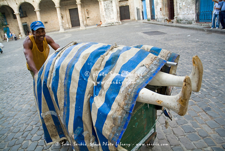 Man pushing a wagon with a mannequin on top through Plaza Vieja, Havana, Cuba.