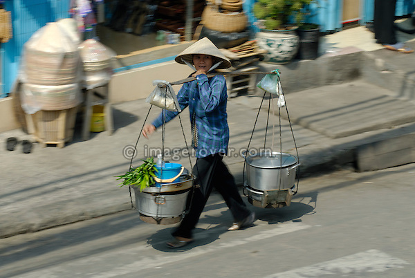Asia, Vietnam, Ho Chi Minh City (Saigon). Asian woman carrying a mobile food stall along Bui Vien St. in the backpackers area around Pham Ngu Lao / Bui Vien St. (District 1).