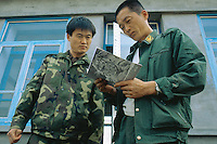 China. Province of Jilin. Li Shu Gou village. A worker, dressed in military clothes, from the Forestry Department distributes to the population leaflets on Siberia Tiger from the Hunchun Nature Reserve.© 2004 Didier Ruef