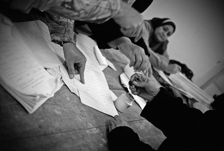 An Egyptian woman who can not read or write signs a voting form with a stamp on the second day of parliamentary elections at a voting station in Abbassia, Cairo, Egypt, Tuesday, Nov. 29, 2011. Tuesday marks the second and final day of the first round of parliamentary elections in Egypt since Hosni Mubarak's ouster, a giant step toward what many in the country hope will be a democratic Egypt after decades of dictatorship.